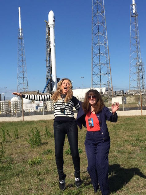 Carol and Colleen jump in the air in front of rocket
