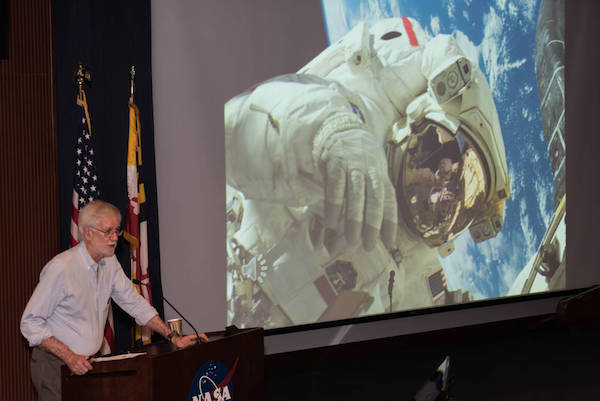 photo of Compton Tucker speaking at a podium in front of a large photo of Piers on a spacewalk